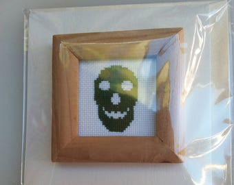 Dark green cross-stitched skull in a wooden frame on a card