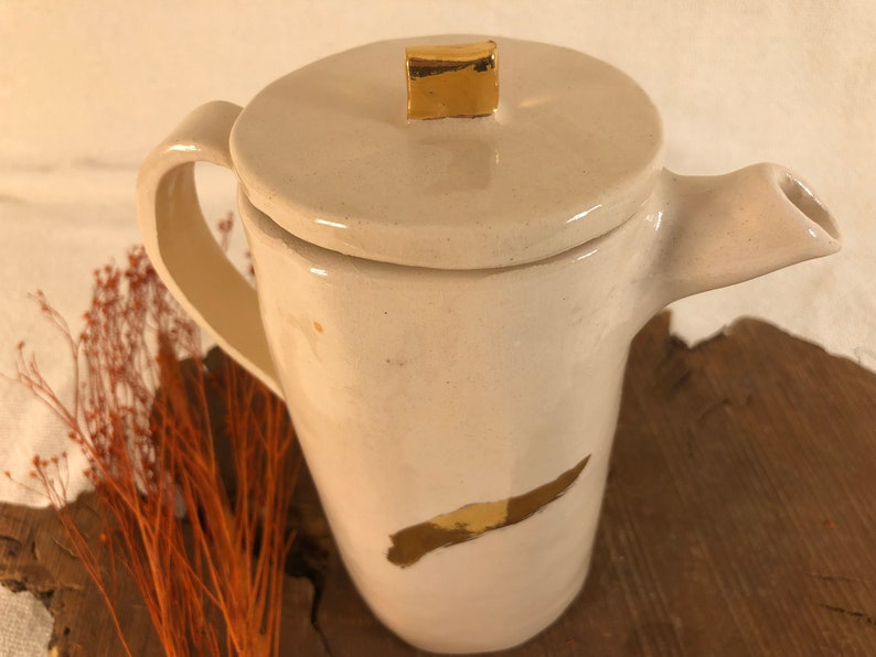 Earthenware teapot with gold decoration.