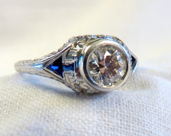 Art Deco Diamond and Platinum Engagement Ring centered with a 0.75 ct Early Modern Round Brilliant Cut Diamond. F Color