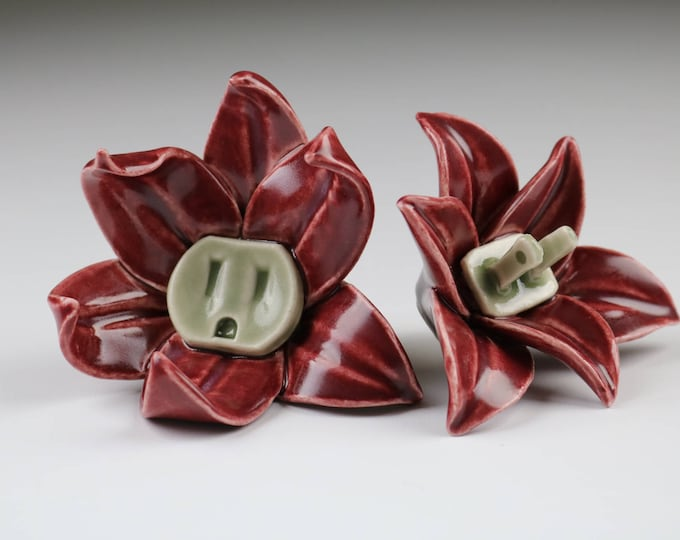 Pair of red Flower Power male and female porcelain wall sculptures