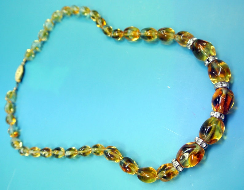 Beautiful vintage 1950s opaque goldyellow graduated oval glass bead necklace with rhinestone spacers and goldcolor metal securety clasp.