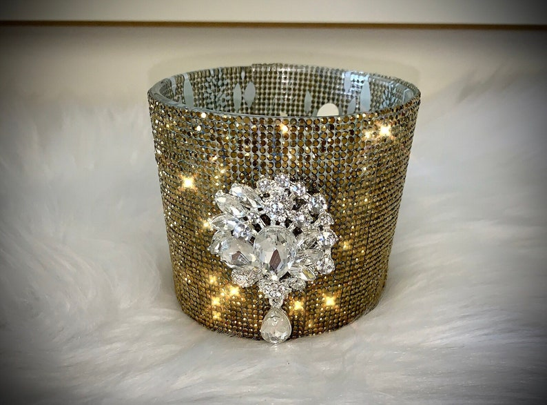 Gold crystal rhinestone container candle with clear crystal drop embellishment.