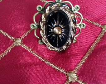 An antique button ring that is adjustable to your size.