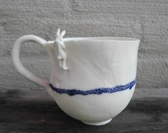 Mug in white porcelain with rabbit looking over the rim - handmade ceramic whimsical mug