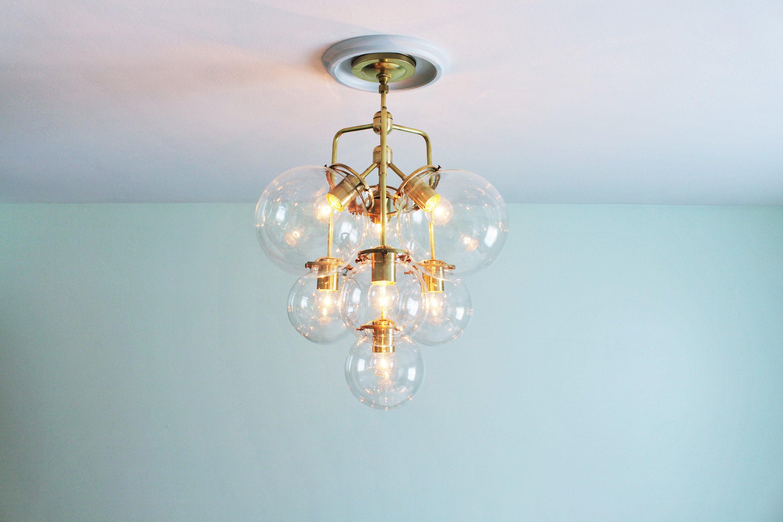 Bubble chandelier 3 tiered globe pendant lighting fixture 7 clear glass globes raw brass finish modern bootsngus lighting decor