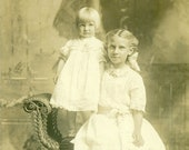 Blonde Sisters White Dress Toddler Standing on Wicker Chair 1910s RPPC Real Photo Postcard Photograph Black White Photo