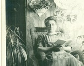 Woman Reading Book Inside Wallpaper Room Mantle Clock Wicker Chair 1910s Antique RPPC Real Photo Postcard Photograph Black White Photo