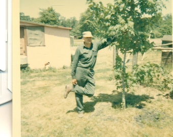Man Holding Up His Leg by Pant Cuff Leaning on a Tree 1960s Photograph Color Photo
