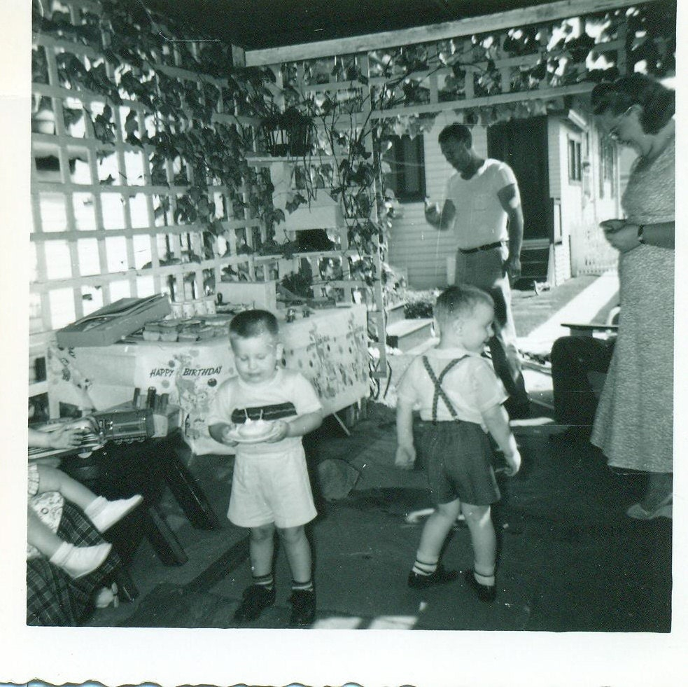 Vintage 1940s little boys at birthday party getting plates of food summer porch black and white photo photograph
