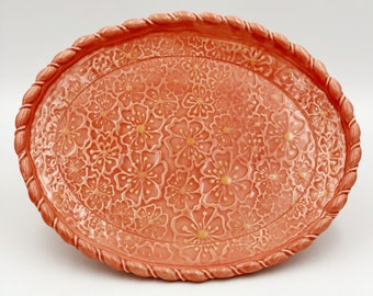 Floral textured pottery platter with bright poppy colored glaze and detailed rim addition