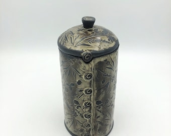 Handmade textured lidded ceramic treasure jar. Tall covered jar with dark brown clay and a honey white glaze wiped from a floral texture