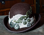 steampunk mini bowler derby hat, brown and cream fascinator, with cogs and clock parts, the engineer
