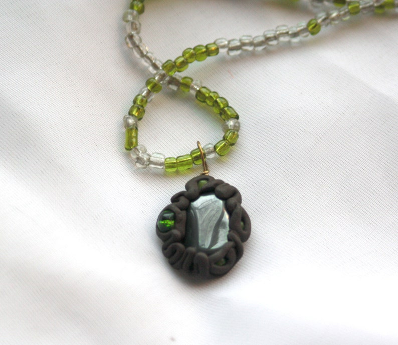 I AM the EARTH PROTECTED Hematite clay wrap pendant on green image 0