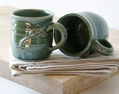 Two stoneware pottery coffee mugs - glazed in forest green with tiny mouse