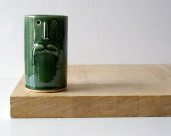 One ceramic vase with face design - glazed in forest green