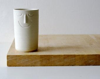 One ceramic vase with sleeping face design - glazed in vanilla cream
