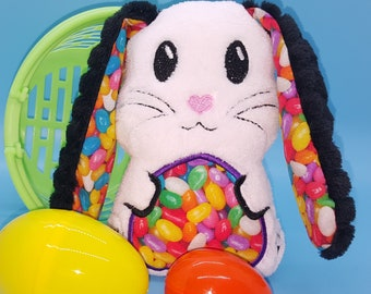 Soft stuffed white with black floppy eared bunny with jelly beans featured in tummy and ear accent fabric