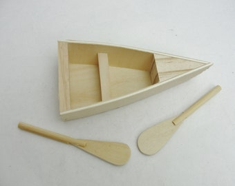 Small wooden rowboat with 2 oars