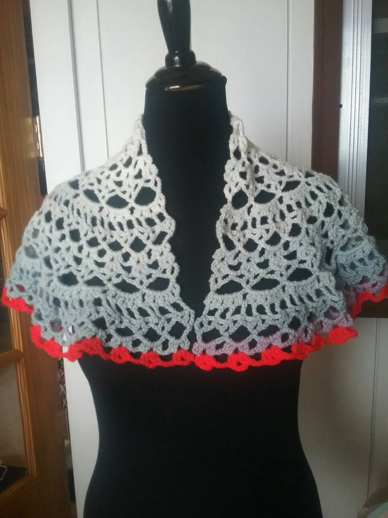 Shawl trimmed in red two fasteners pins one red one blue crocheted by hand.