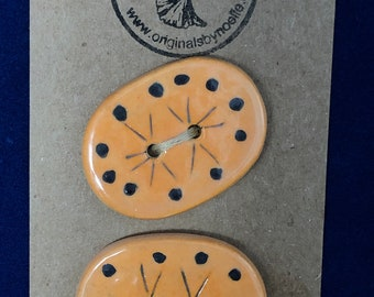 Large Orange Oval Buttons With Black Dots and Lines