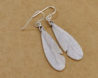 Handmade sterling silver earrings with vintage native Navajo carved stone feather charms, long feather dangler earrings.