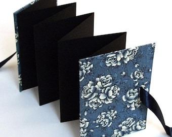 blue accordion book with floral pattern, gift idea for grandparents holding 14 photos, small photo album