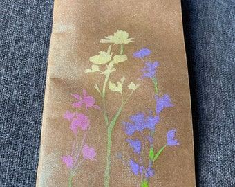 Spring wildflowers in yellow pink and purple on holographic shimmer journal lined notebook