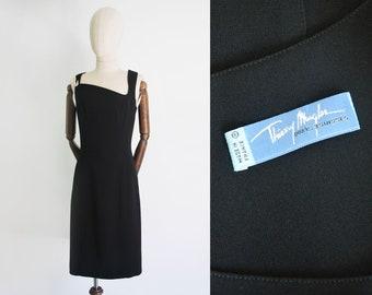 bb9d7b624b9c Vestido THIERRY MUGLER. Negro básico super favorecedor. Escote diagonal con  broche plateado firmado. Tejido 100% poliéster