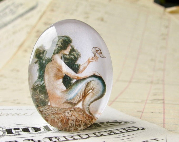 Mermaid holding a shoe, wishing for legs, long black hair, handmade glass oval cabochon, 25x18 or 40x30mm, Magical Maidens collection