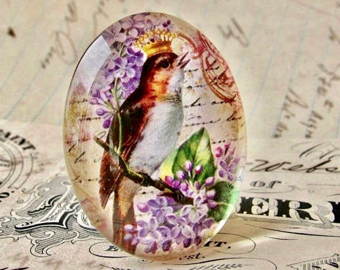 Songbird with crown and lilacs, from our Beautiful Birds collection of handmade glass cabochons, 40x30mm, purple flowers, vintage script
