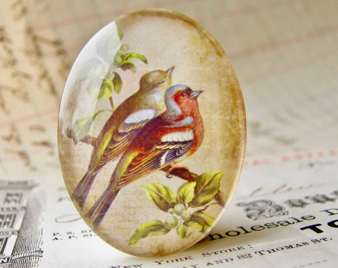 Pair of birds perched on a branch, from our Beautiful Birds collection of handmade glass cabochons, 40x30mm oval cabochon, red, green
