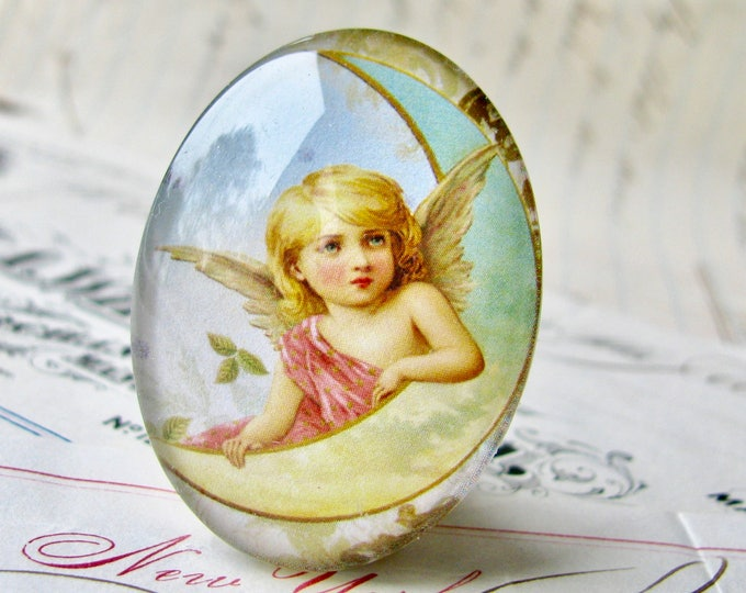 Victorian angel on the moon, handmade in this shop, glass oval cabochon, 40x30mm or 25x18mm, winged cherub, sky blue, yellow