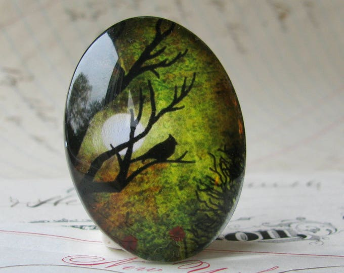 Bird in a tree silhouette against full moon, 40x30mm handmade glass oval cabochon, olive green sky, sunset, from our Mystic Moon collection