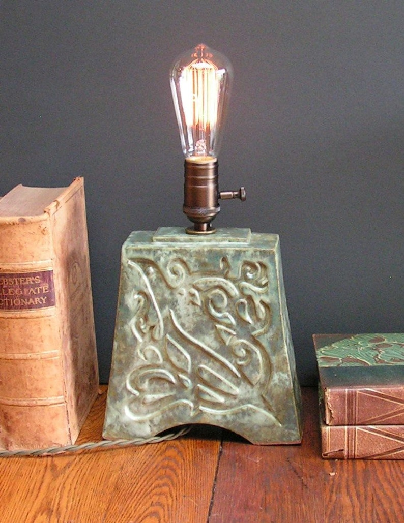 and indented Art Nouveau design of a bird mottled green glaze Stoneware lamp with vintage Edison bulb