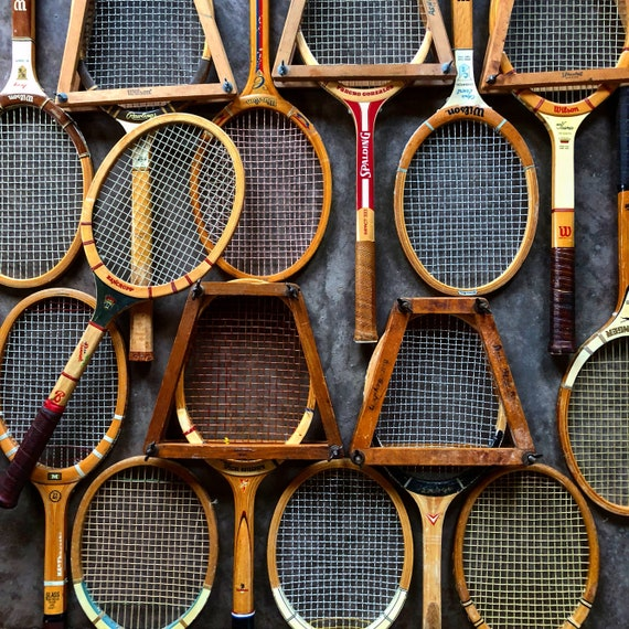 a wall full of vintage wooden tennis racquets