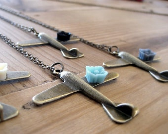 lost...a very special antique brass plane necklace, with a black, ivory, gray or turquoise cute flower