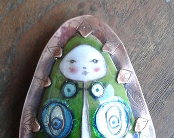 Baby in a mothskin cloak. Green enamel brooch.