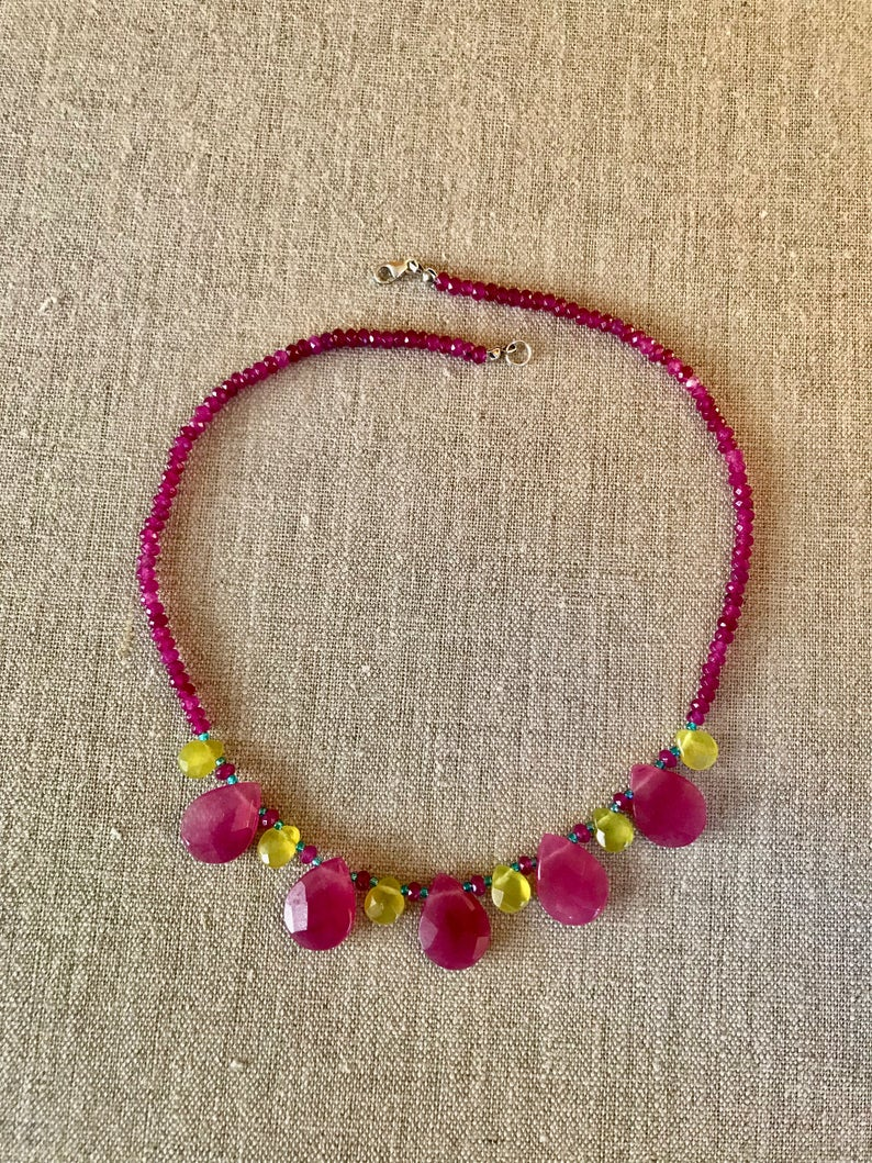 A lovely pink jade stone beaded necklace accented with yellow jade teardrop beads .