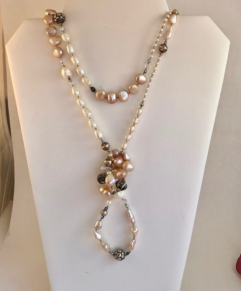 Necklace of stunning rows and rows of fresh water pearls Pearls are accented by crystals and quality sterling silver beads.