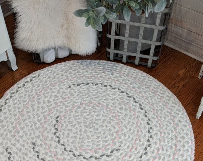 blush pink and sage green, on a background of light ash gray and white braided nursery rug from  super soft cotton