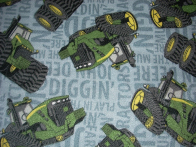 2 layers of fleece John Deere Diggin  green tractors and equipment on light Blue- Fleece Blanket 70 x 59 Finished Sewn Edges