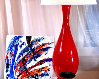 A abstract fabric painting in a minimalist style. Bold slashes of color, red, blue and black are set against a white background.