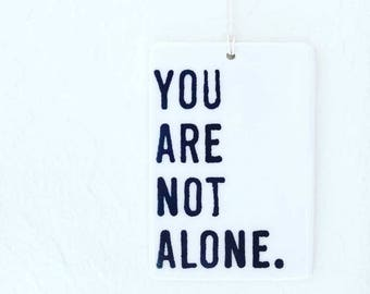 porcelain tag screenprinted text you are not alone.