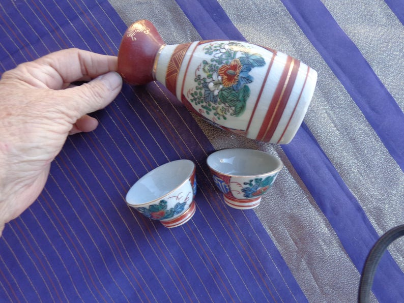 two cups and sake container Enlarge for detail Vintage Sake set Signed   Scene has flower on one side and Four Japanese  Men on other