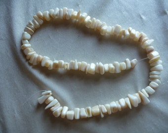 Beads, Mother of Pearl, Medium-Large Chips, Natural Bleached/White. Sold per 16 inch strand. There are 100 beads on the strand.