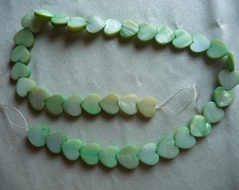 Beads, Mother of Pearl, 12mm Flat Heart, Shades of Green. Sold per 15 inch strand. Total of 37 beads on strand.