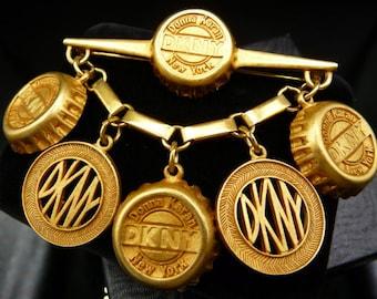 DKNY bottle cap dangle brooch pin, Donna Karan New York subway tokens, Russian matte gold, 1980s vintage