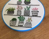 Hand embroidered hoop wall hanging, cacti succulent house plants in hoop wall hanging, monochrome pots with green and pink plants