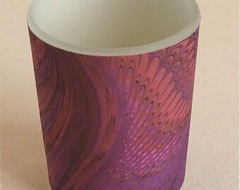 Deep purples swirl around a votive light