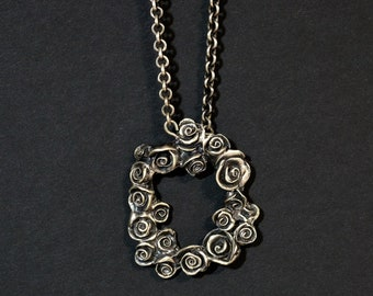 roses frame reversible silver pendant on a cable chain